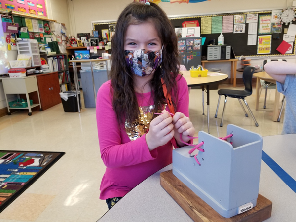 [PIC] Pawling Elementary Student Alexis Caceres Works With A Shoelace Tieing Model Provided By BOCES Construction Trade Students