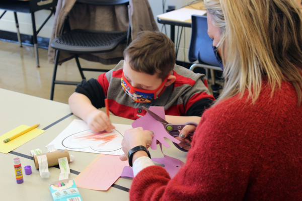 [PIC] Salt Point Center Teaching Assistant Kelsey Butkiewicz helps her students with coloring hearts