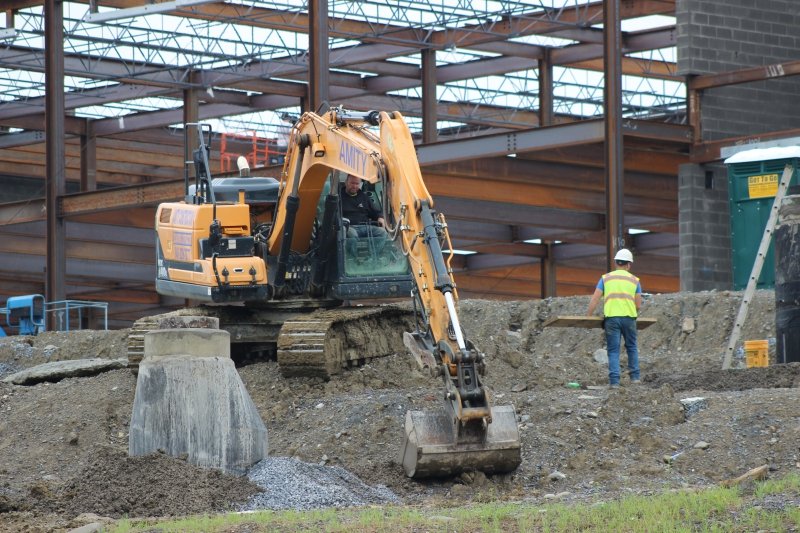 An extractor moves dirt at CTI as part of the capital project.